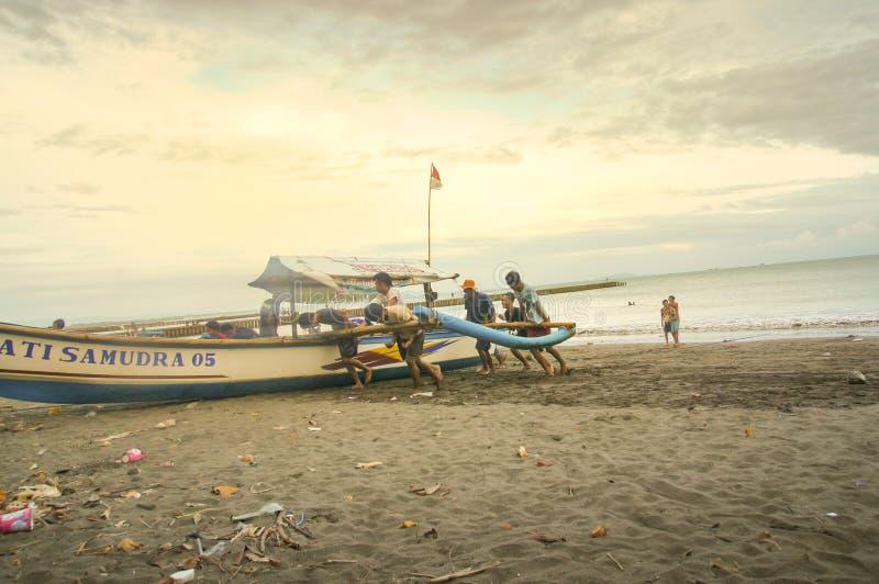 推挤他们的小船的Fishermans对海滩 宽低角度视图 免版税库存照片