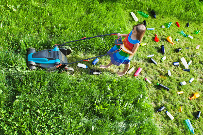 推挤割草机和留下塑料废弃物的女孩后边 图库摄影