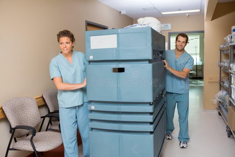 推挤台车的护士,当同事协助时 免版税库存照片