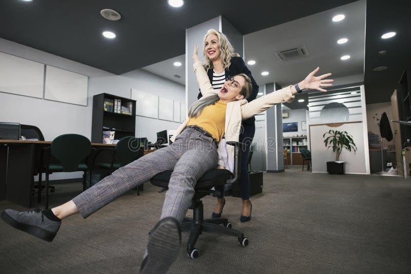 推挤同事的愉快的妇女坐办公室椅子 免版税库存照片