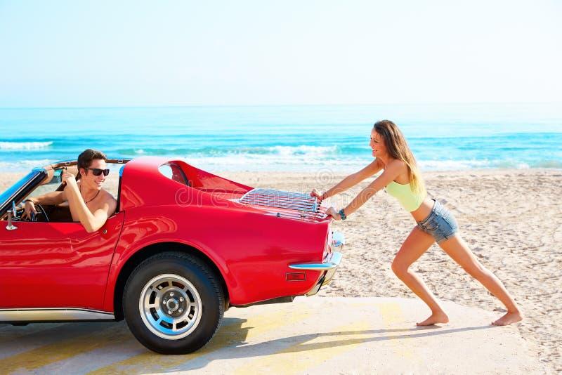 推挤在海滩滑稽的人的女孩一辆残破的汽车 免版税库存照片