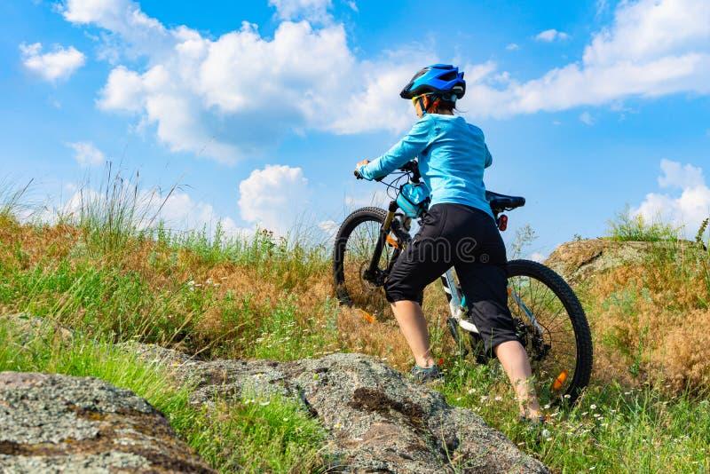 推挤她的一个陡坡的妇女骑自行车者自行车 免版税库存图片