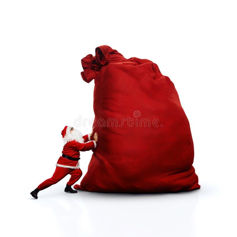 推挤巨大的大袋的圣诞老人 查出在白色 图库摄影