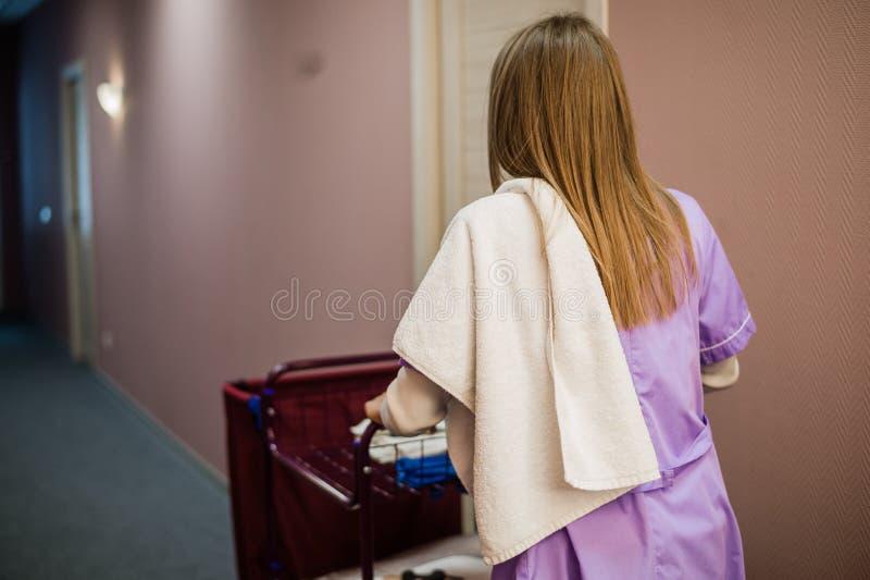 推挤推车的年轻女性佣人,当清洗旅馆客房时 库存图片