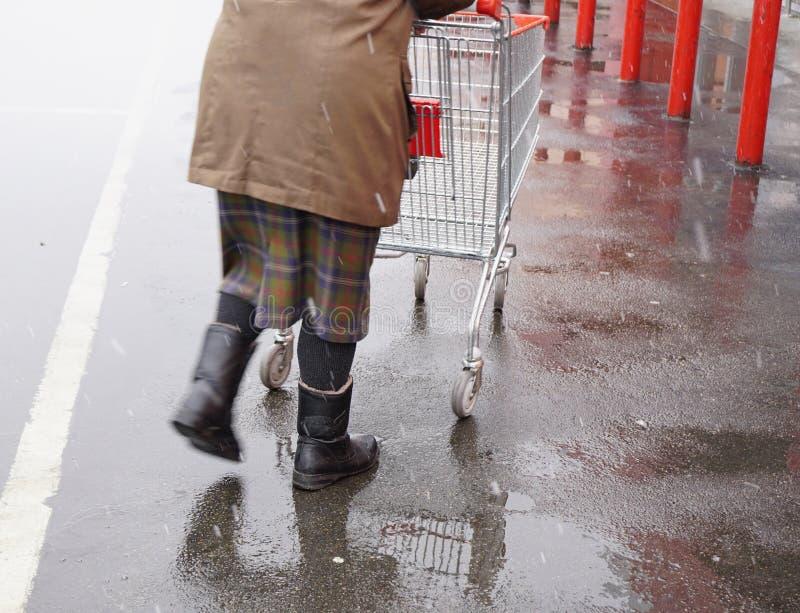 推挤推车 棕色夹克的剪影妇女在超级市场附近推挤杂货的空的金属推车 免版税图库摄影