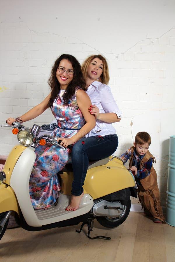推挤有两个女朋友的小男孩一辆滑行车,演播室照片 图库摄影