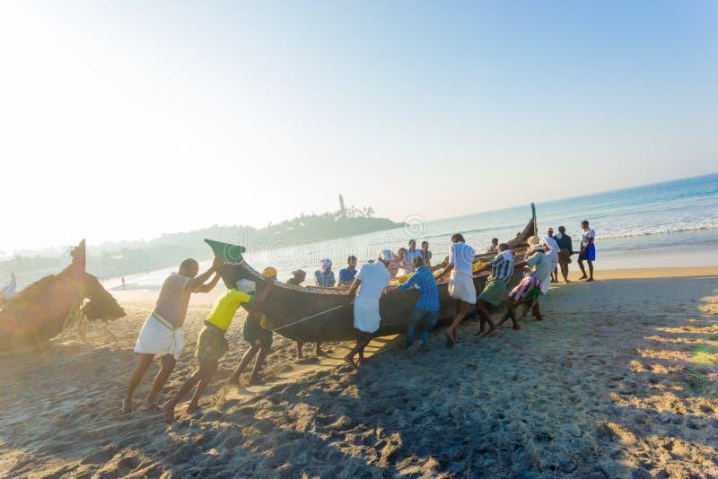 推挤渔船海滩的科瓦兰村民 免版税库存图片