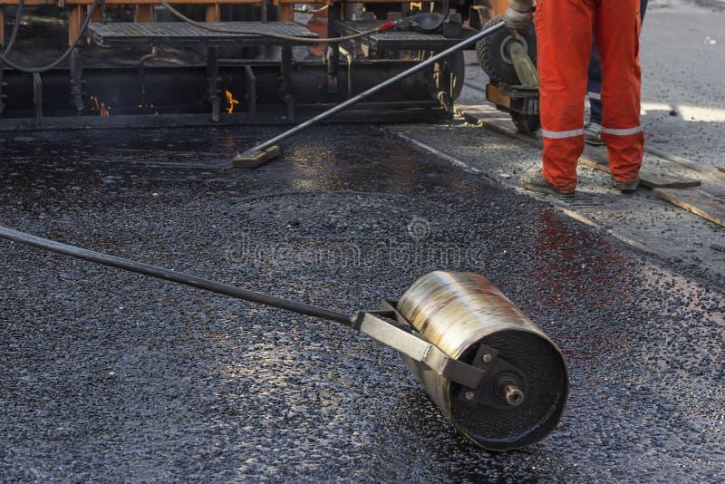 推挤石油沥青砂胶铺的手路辗 免版税图库摄影