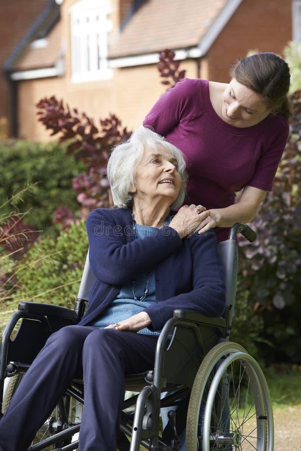 推挤轮椅的女儿资深母亲 库存图片