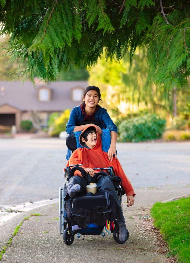 推挤轮椅的姐妹残疾弟弟在邻里附近 免版税库存图片