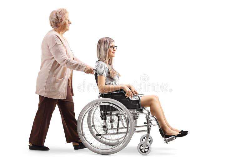 推挤轮椅的年长妇女一年轻女人 免版税库存照片
