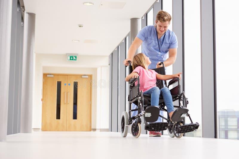 推挤轮椅的护士女孩沿走廊 免版税库存图片