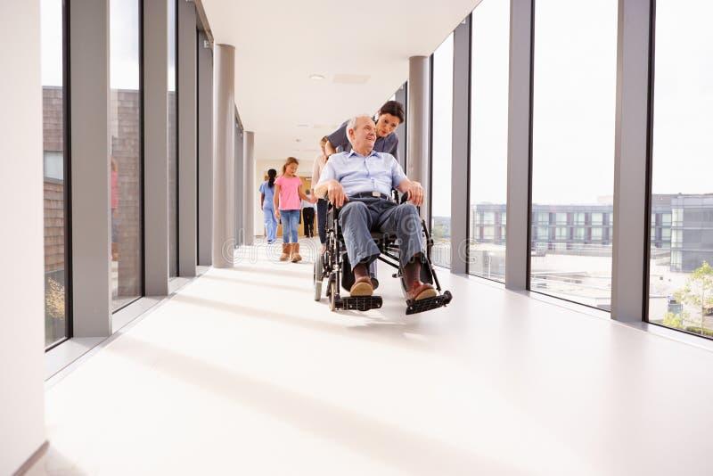 推挤轮椅的护士资深患者沿走廊 免版税图库摄影