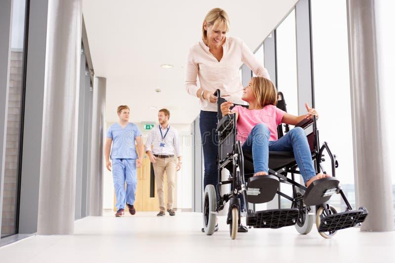 推挤轮椅的母亲女儿沿走廊 免版税库存照片