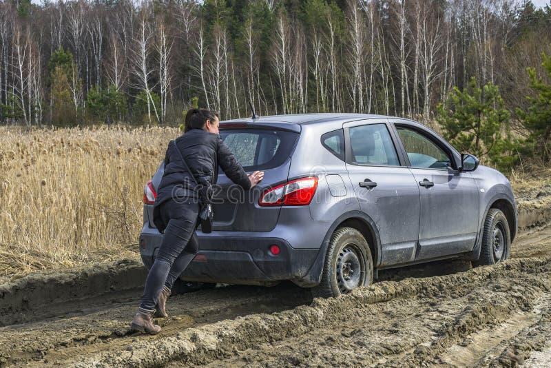 推挤陷进的汽车的女孩在沼泽土路 库存照片