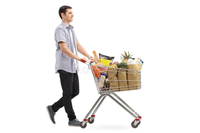推挤购物车的年轻人用杂货填装了 免版税库存照片