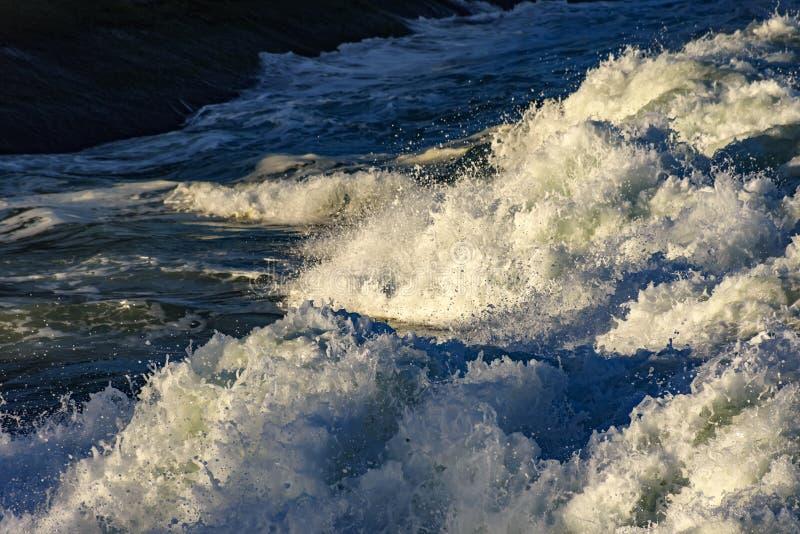 推进在岩石的波浪泡沫 免版税库存图片