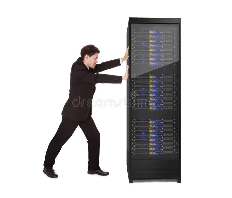 推进服务器机架的生意人 免版税库存图片