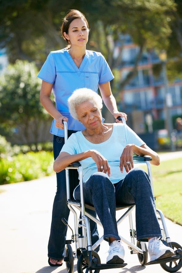 推进轮椅的护工不快乐的高级妇女 免版税库存照片