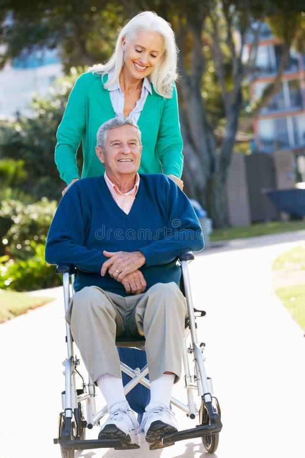推进轮椅的高级妇女丈夫 库存图片