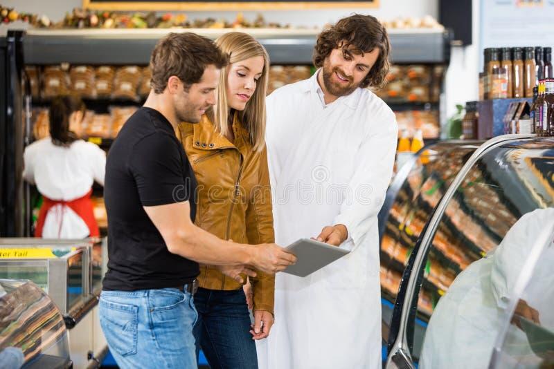 推销员和夫妇使用数字式片剂在 免版税库存图片