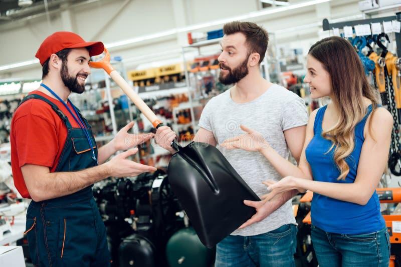 推销员在电动工具商店显示客户新的showel夫妇  免版税库存照片