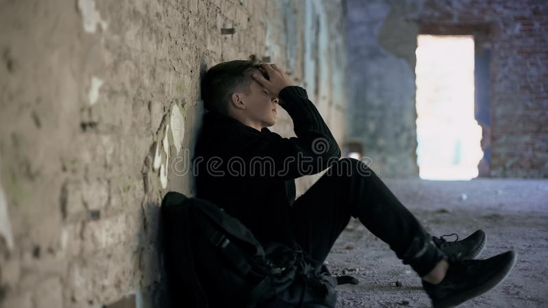 掩藏从胁迫的沮丧的青少年在被放弃的房子,困难的青春期 库存图片