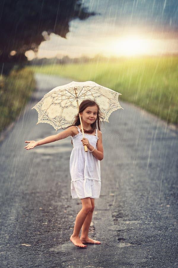 掩藏从雨的愉快的女孩在伞下 免版税库存图片