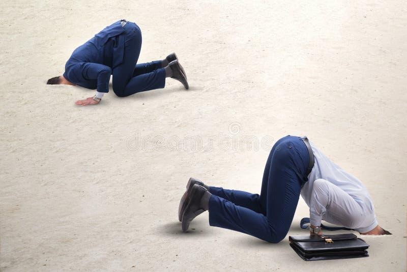 掩藏他的头的商人在逃脱从问题的沙子 库存照片