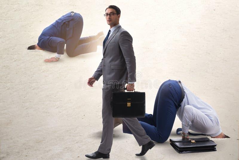 掩藏他的头的商人在逃脱从问题的沙子 免版税图库摄影
