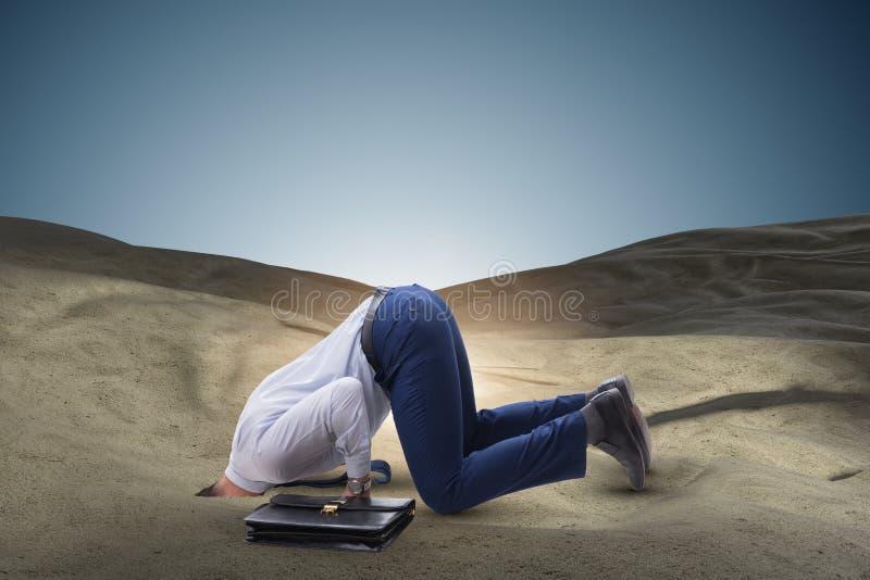 掩藏他的头的商人在逃脱从问题的沙子 免版税库存照片