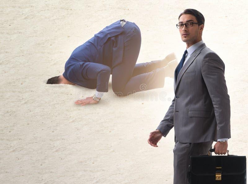 掩藏他的头的商人在逃脱从问题的沙子 库存图片