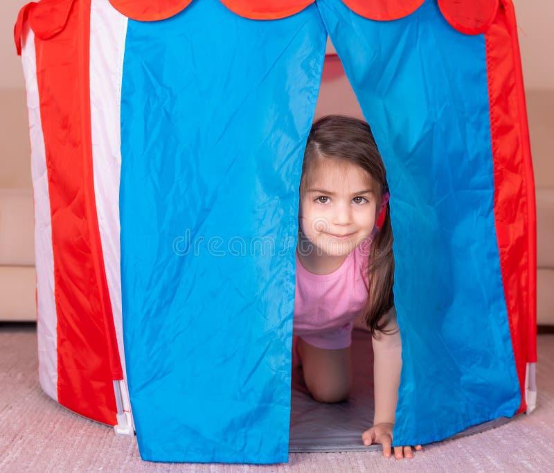 掩藏在一个五颜六色的玩具帐篷的逗人喜爱的女孩戏剧画象  免版税图库摄影