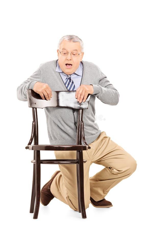 掩藏在一把木椅子后的害怕的绅士 库存图片