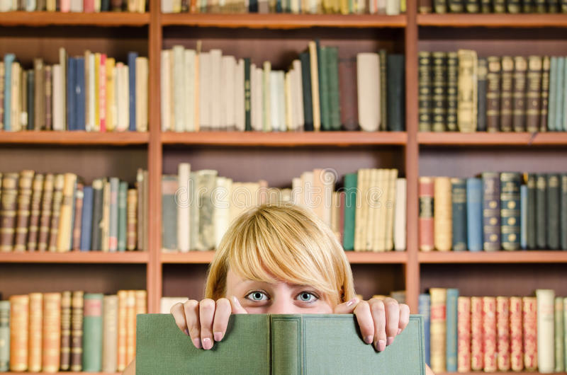 掩藏在书后的好白肤金发的女孩 免版税图库摄影