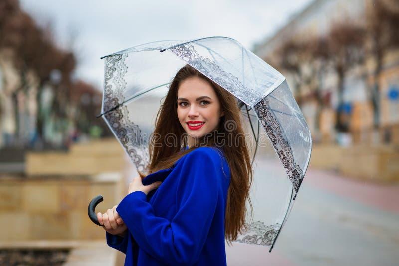 掩藏在伞下的年轻美丽的女孩画象  库存照片