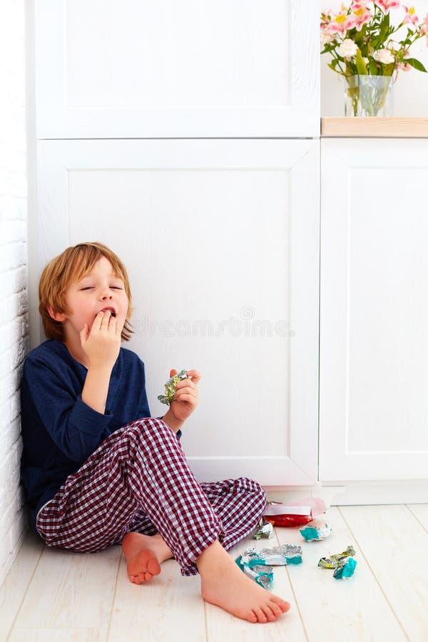 掩藏在厨房角落的爱吃甜品的胃口孩子,吃糖果 免版税库存图片