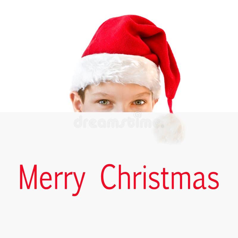 掩藏在圣诞快乐后的红色圣诞老人帽子的年轻男孩 免版税库存照片
