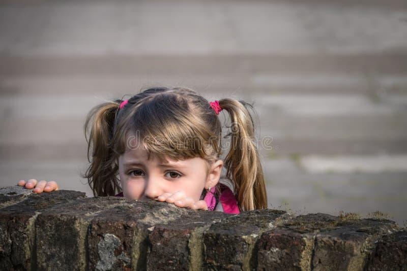 掩藏在墙壁后的女孩 免版税库存图片