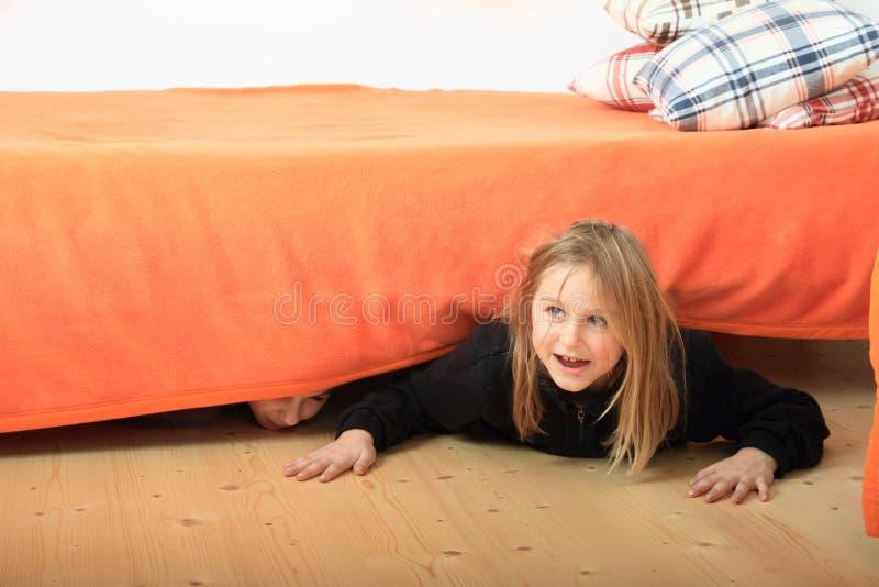 掩藏在床下的孩子 库存图片