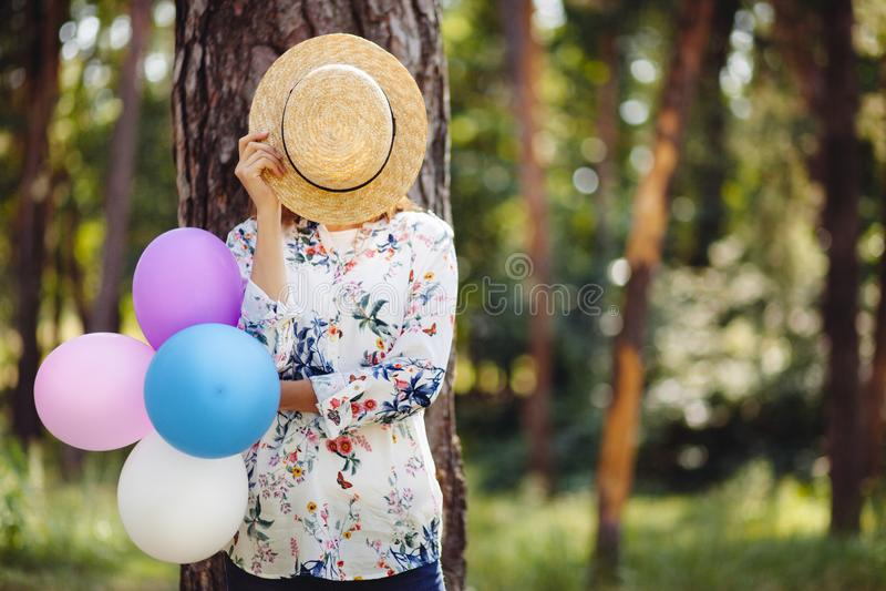 掩藏在有五颜六色的气球的草帽后的年轻女人在自然 库存照片