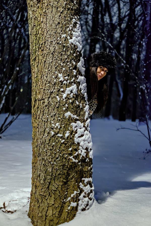 掩藏在树后的女孩在一个多雪的晚上 库存图片