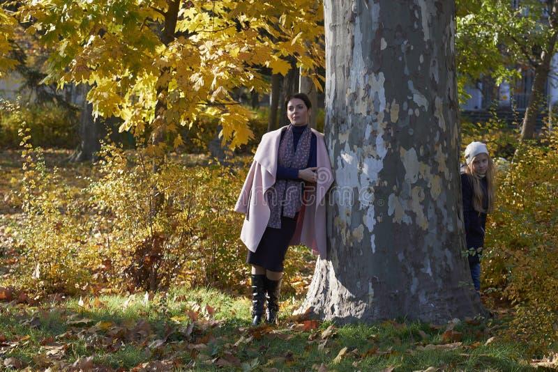 掩藏在树后的母亲和小女孩 图库摄影