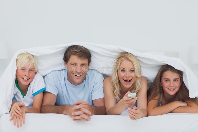 掩藏在毯子下的快乐的家庭 免版税库存照片