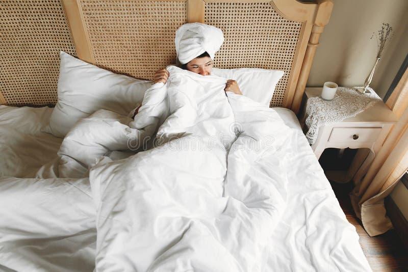 掩藏在白色板料下的美丽的愉快的年轻女人,说谎在床上在酒店房间或家庭卧室 有白色毛巾的时髦的女孩 库存图片
