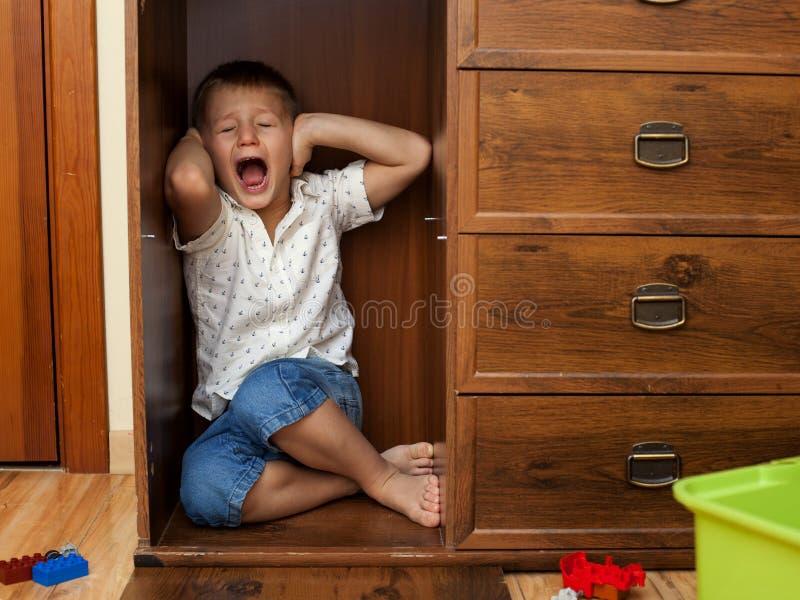 掩藏在碗柜和哭泣的小男孩 库存照片