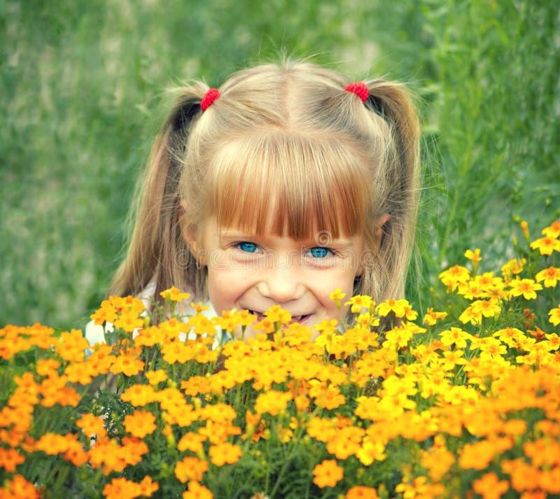 掩藏在花后的小女孩 免版税库存照片