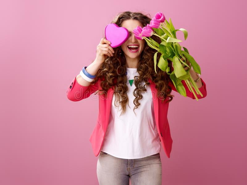 掩藏在花束和心形的箱的妇女巧克力后 免版税库存照片