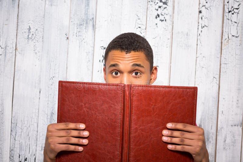 掩藏在记数器或学报后的英俊的人在演播室 免版税库存照片