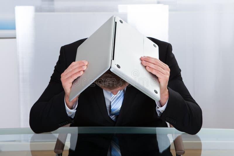 掩藏在他的膝上型计算机下的沮丧的商人 库存图片